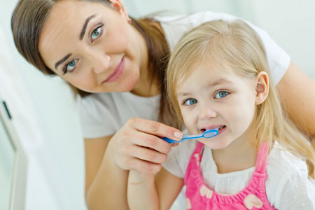 Mom and Daughter brushing their teeth - Dentist in Huntsville, AL